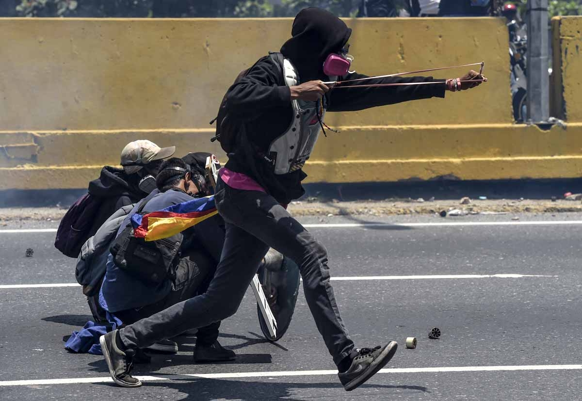 Opposition activists clash with riot police during a protest in Caracas on April 26, 2017.