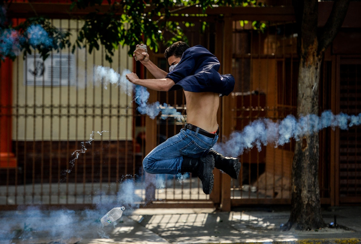 An opposition activist thows a stone at riot police during clashes following a protest against President Nicolas Maduro in Caracas on April 26, 2017.