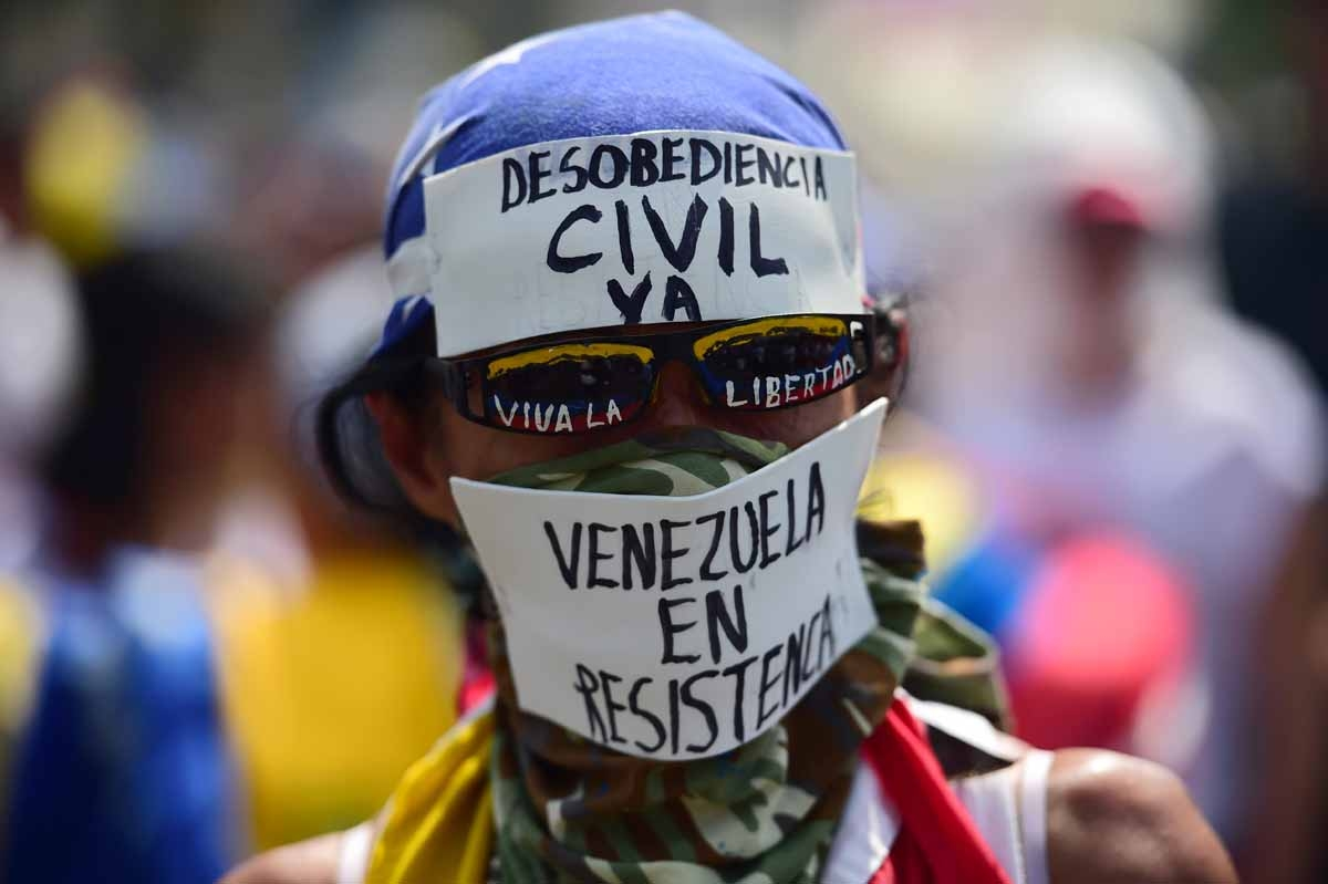 A demonstrator against President Nicolas Maduro's government calls to Civil Disobedience during a protest at the east side of Caracas on April 19, 2017.