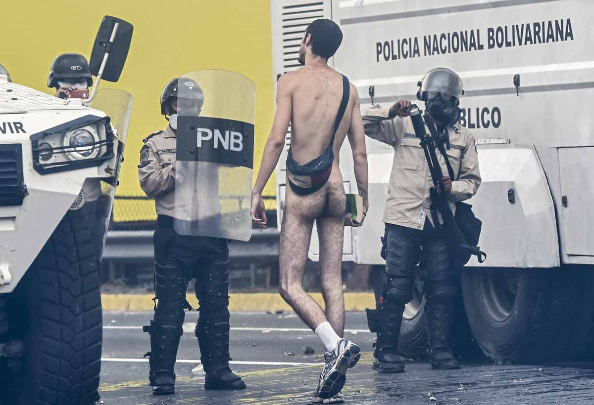 A naked demonstrator remonstrates with riot police during a protest against Venezuelan President Nicolas Maduro, in Caracas on April 20, 2017.