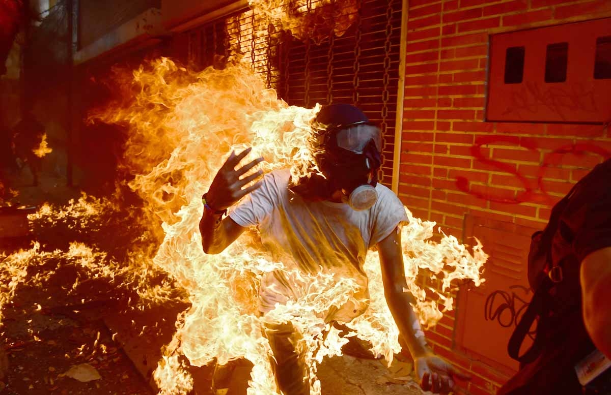 A demonstrator catches fire during clashes with riot police within a protest against Venezuelan President Nicolas Maduro, in Caracas on May 3, 2017. Venezuela's angry opposition rallied Wednesday vowing huge street protests against President Nicolas Madur
