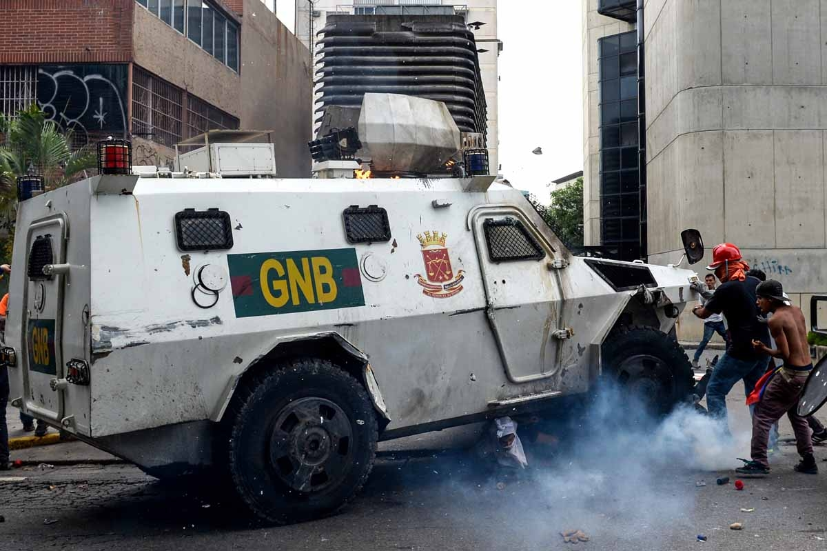 A Venezuelan National Guard riot control vehicle runs over an opposition demonstrator during a protest against Venezuelan President Nicolas Maduro, in Caracas on May 3, 2017.