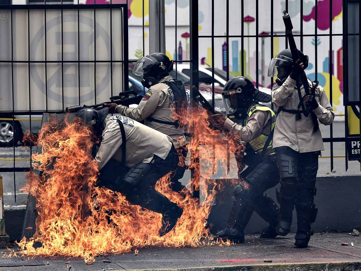 A group of riot policemen are hit by a Molotov cocktail hurled by an opposition demonstrator during a protest against President Nicolas Maduro, in Caracas on May 8, 2017.