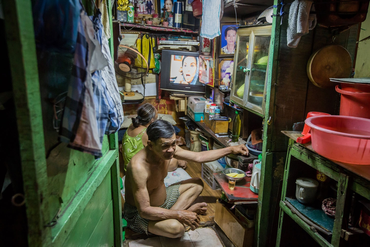 Kha Tu Ngoc (back) watches television sitting next to her husband Pham Huy Duc in their two-square-meter house in Ho Chi Minh City on May 2, 2018.