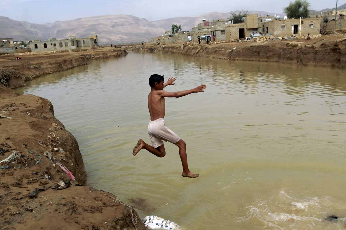 A Yemeni boy dives into a flooded field following heavy rain fall, in the city of Amran, 50 kms north of Sanaa, on April 15, 2016.