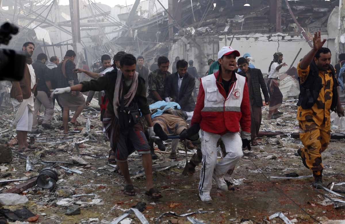 Yemeni medics and rescue workers carry a body on a stretcher amid the destruction of a funeral hall at the site of reported airstrikes by Saudi-led coalition air-planes in the capital Sanaa on October 8, 2016.