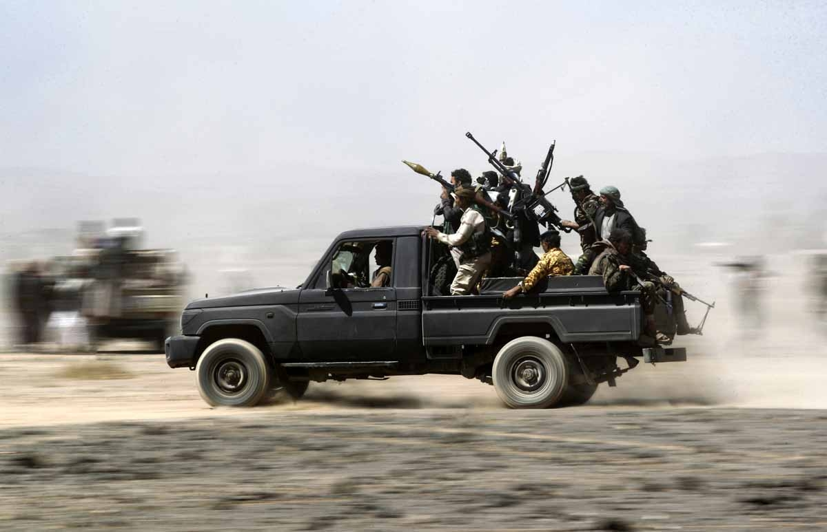 Armed Yemeni tribesmen loyal to the Shiite Huthi rebels sit in the back of an armed vehicle during a gathering to mobilise more fighters into several battlefronts on November 1, 2016 on the outskirts of the capital Sanaa.