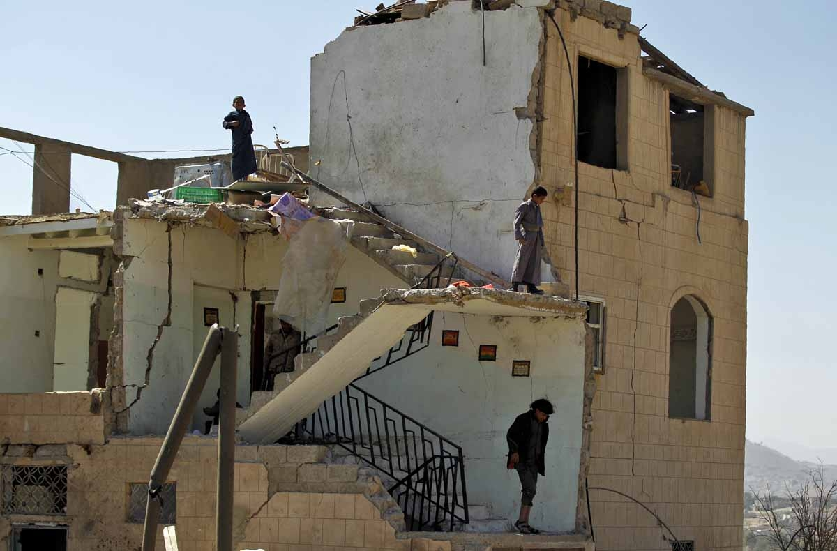 Boys wander amidst the rubble of a house destroyed by Saudi-led coalition air strikes two days earlier on the outskirts of the Yemeni capital Sanaa on November 14, 2016.