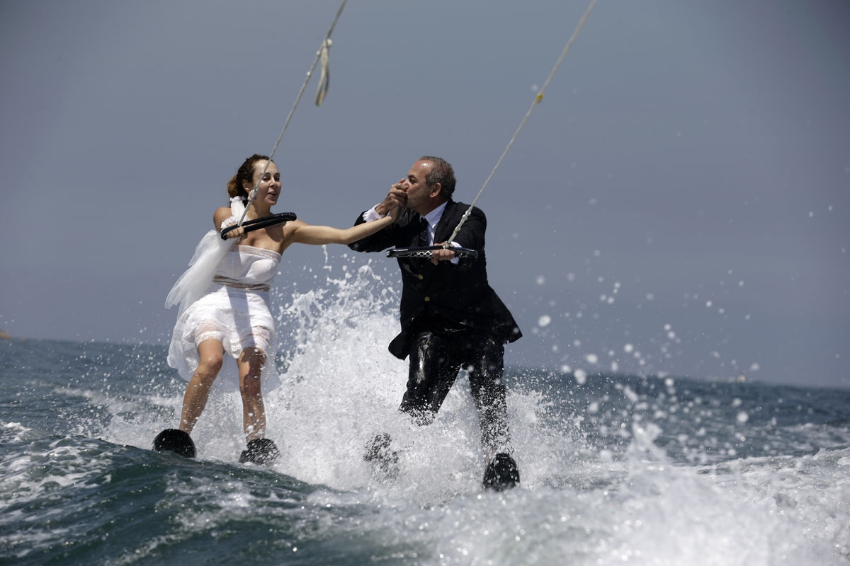 Lebanese groom Tommy kisses the hand of his bride Nadine's while water skiing dressed in their wedding clothes in the waters off the bay of Jounieh, north of Beirut, on May 29, 2017.