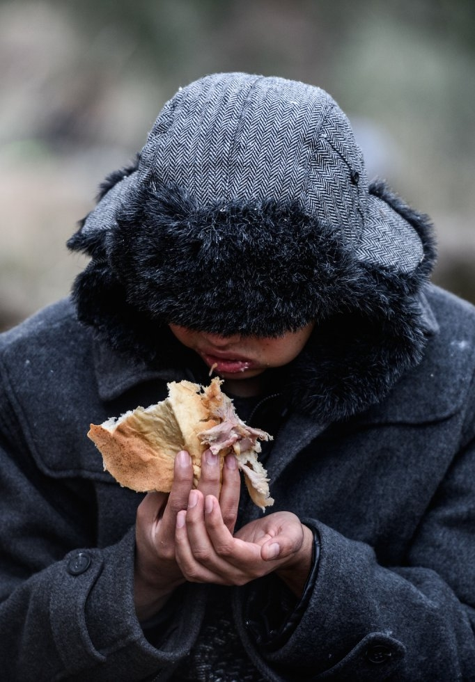 A refugee boy eats while camping after migrants were cheated by smugglers. January 29, 2016.
