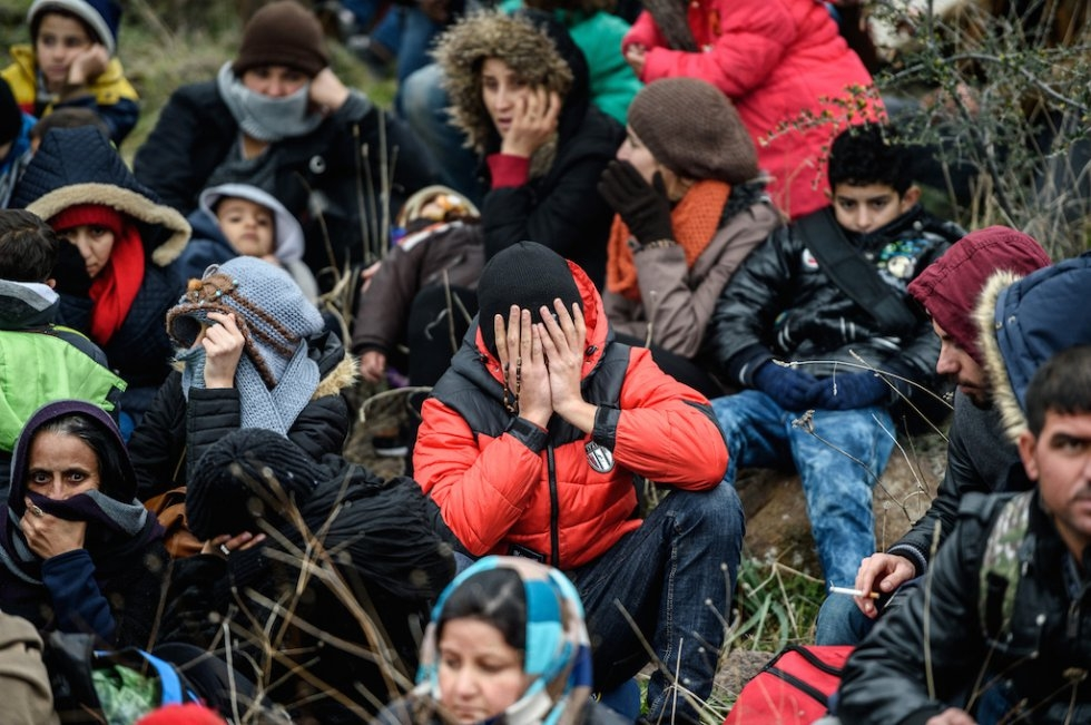 Migrants wait in the woods after being cheated by smugglers. January 29, 2016.