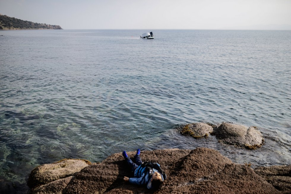 The body of a drowned refugee child lies on the beach. The sunken boat is in the background. January 30, 2016. (AFP/Ozan Kose)