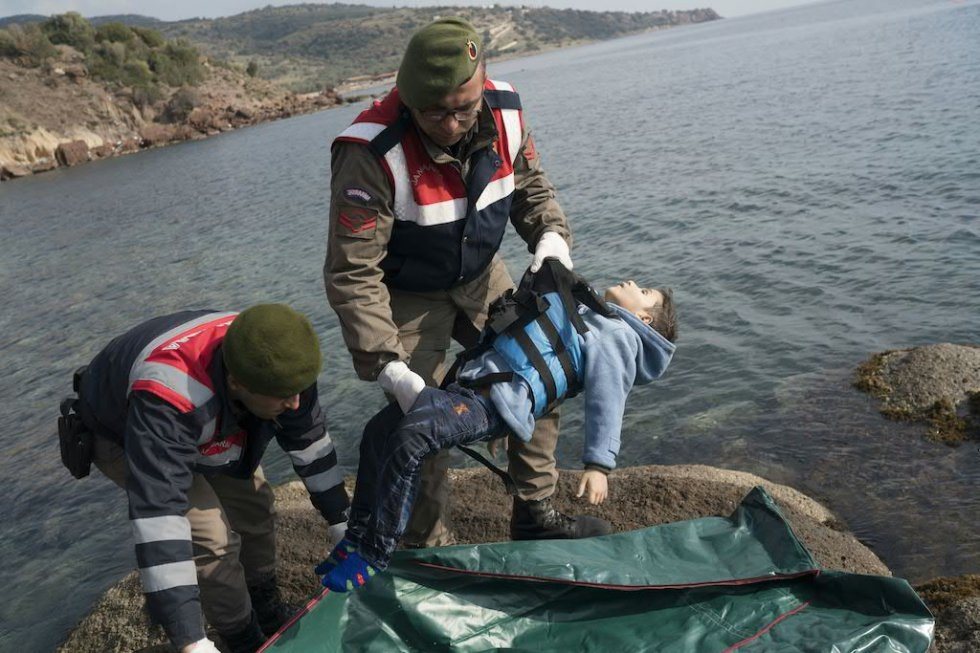 Turkish policemen put the body of a drowned refugee baby into a body bag. January 30, 2016. (AFP/Ozan Kose)