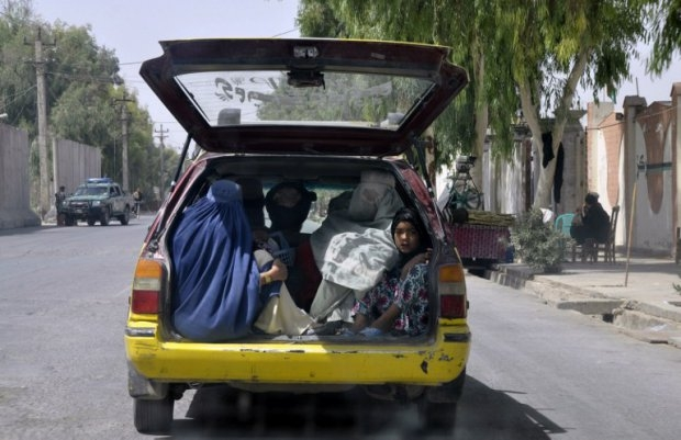 Afghan women ride in the back of a taxi in a street in Kandahar on September 16, 2013. (AFP Photo/Siddiqullah Alizai)