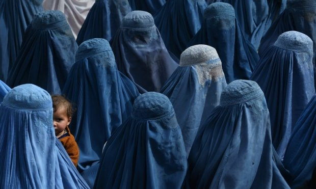 An Afghan woman holds her baby as she and supporters attend the election rally of Afghan presidential candidate Abdullah Abdullah in Jalalabad on February 18, 2014.