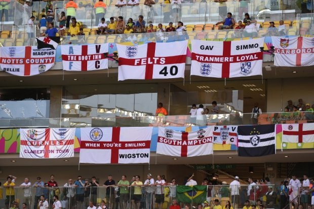 England fans hang flags as they await the kick-off of a Group D football match between England and Italy at the Amazonia Arena in Manaus during the 2014 FIFA World Cup on June 14, 2014.