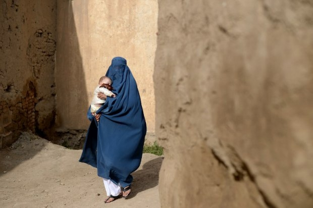 A burqa-clad Afghan villager carries a small child as she walks among a collection of destroyed buildings in the village of Deh Saqi on The Shomali Plains some 20 kms north of Kabul.