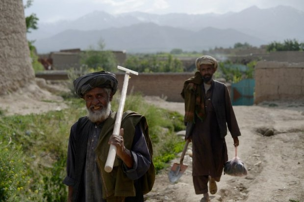 Afghan farmers near destroyed buildings in the village of Deh Saqi on The Shomali Plains
