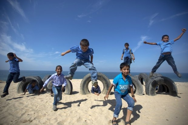 Last year: Palestinian school children play with on Gaza beach on October 24, 2013 in Deir al-Balah.
