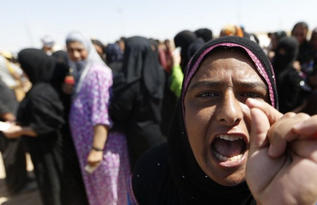 A displaced Iraqi woman shouts as she waits to register at a temporary camp set up to shelter people fleeing violence in northern Iraq on June 17, 2014 in Aski kalak, 40 kms west of the Kurdish autonomous region's capital Arbil. (AFP Photo/Karim Sahib)