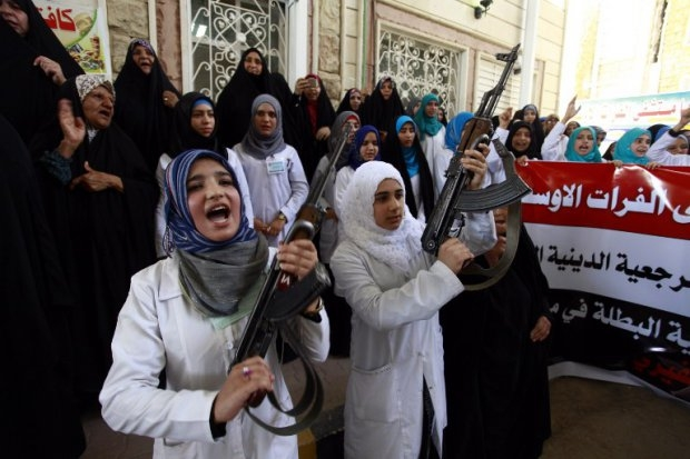 Iraqi Shiite women hold their weapons as they gather in Najaf to show their willingness to join Iraqi security forces in the fight against jihadist militants.