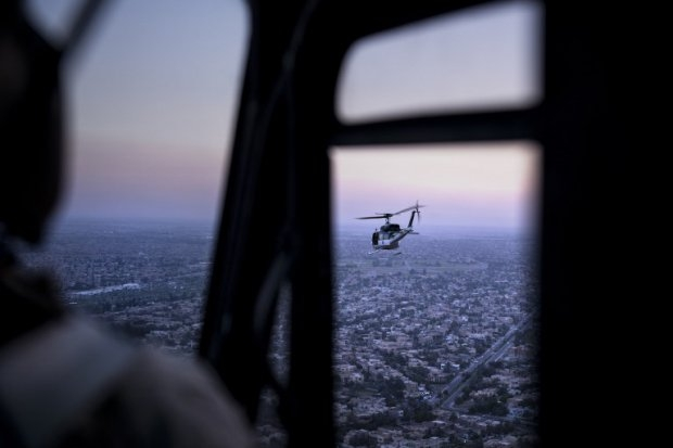 A picture taken on board a helicopter shows an US State Department helicopter flying over the Iraqi capital Baghdad as it transports Kerry.