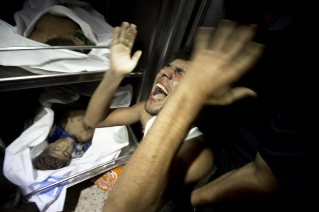 Relatives of four Palestinian boys, all from the Bakr family, mourn over the body of one of the boys at the morgue of al-Shifa hospital in Gaza City, on July 16, 2014. (AFP Photo/Mahmud Hams)
