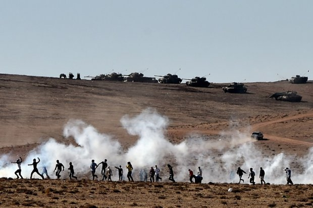 Kurdish people and the Turkish army clash near the border zone on October 7, 2014
