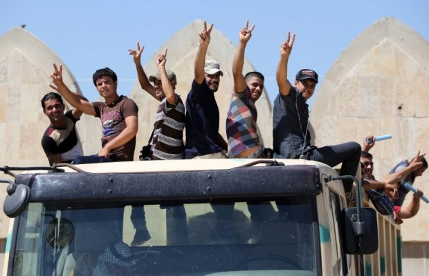 Iraqi volunteers to fight along side the Iraqi security forces against Jihadist militants, flash the sign of victory as they leave a recruitment center. (AFP Photo/Ahmad Al-Rubaye)
