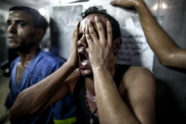 A relative reacts after seeing the bodies of three Palestinian children, killed in an explosion in a public playground on the beachfront of Shati refugee camp. July 28, 2014. (AFP Photo/Marco Longari)