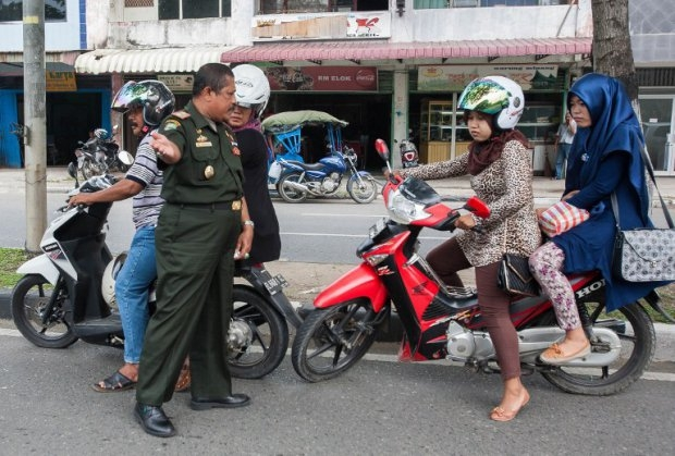 A sharia policeman stops motorists wearing tight trousers in Banda Aceh on September 18, 2014 (AFP Photo / Chaideer Mahyuddin)