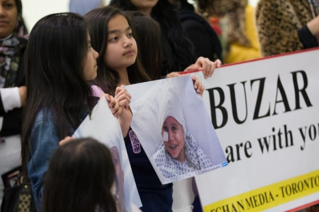Family and well wishers hold portraits of Abuzar Ahmad as they await the child's arrival at Pearson Airport in Toronto, Ontario, Canada, on April 30, 2014