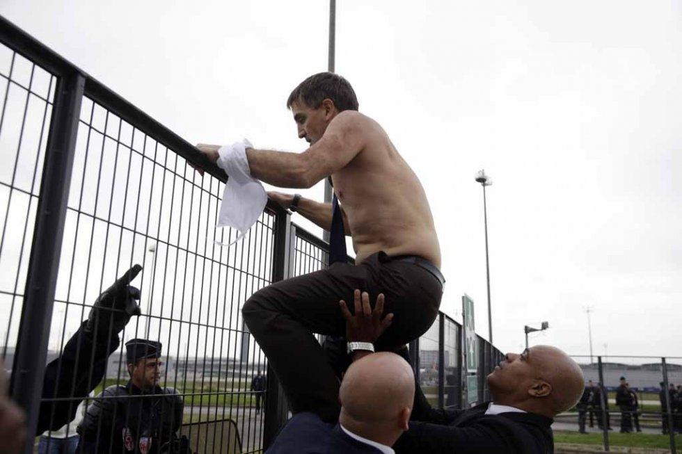 Air France human resources chief Xavier Broseta, his clothes torn, scales a fence to escape a crowd of angry employees. (AFP/Kenzo Tribouillard)