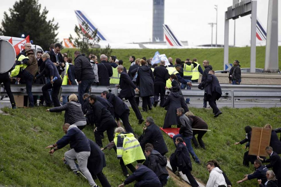 A crowd of Air France employees charges up a hill.