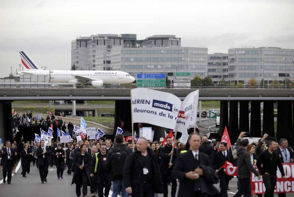 Air France employees march through the airport, protesting planned job cuts.