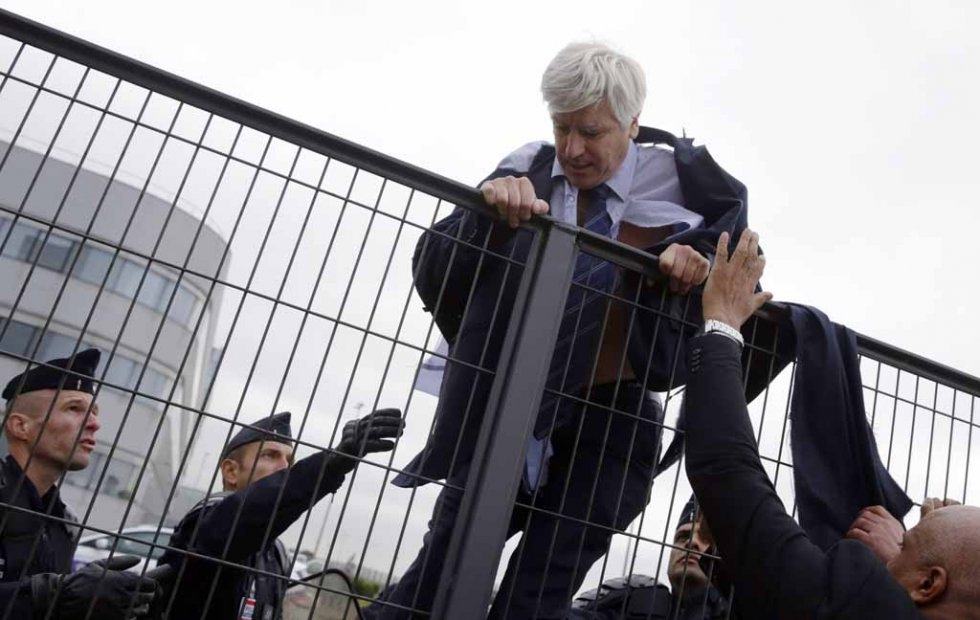 Senior Air France executive Pierre Plissonnier scales a fence to flee a mob of employees.