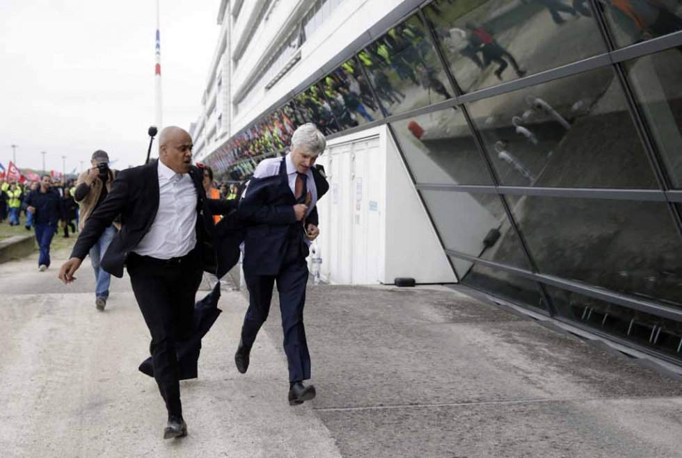 Senior Air France executive Pierre Plissonnier flees a mob of employees.