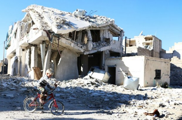 A boy rides his bike past a destroyed building in Aleppo on November 5, 2014