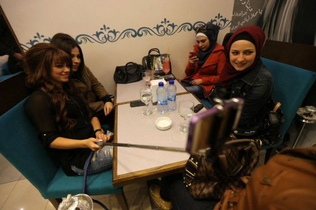 Syrian women take selfies at Fairuz restaurant in Aleppo's government-held Mogambo neighourhood on November 15, 2014