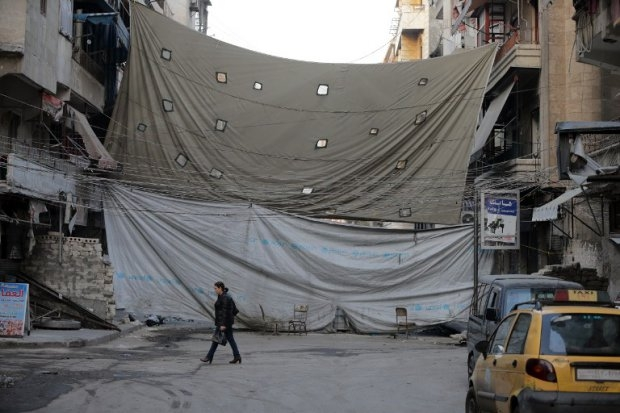 A Syrian woman in the government-held side of Aleppo in a street protected by huge canvas which residents have stretched across it to make it hard for rebels to see them. November 18, 2014 (AFP PHOTO/JOSEPH EID)