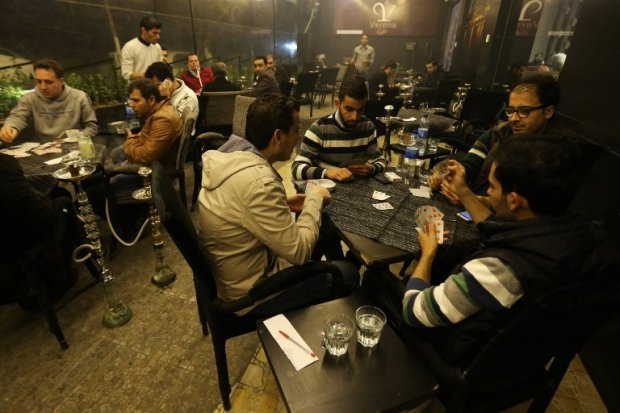 Syrian men play cards at a cafe in the Mogambo neighbourhood on the government-held side of Aleppo on November 15, 2014