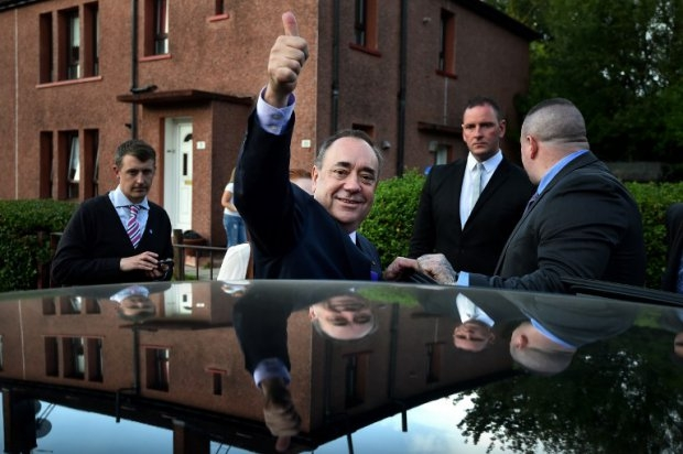 Scotland's First Minister Alex Salmond gestures as he leaves following a visit to a housing estate in Glasgow on September 13, 2014