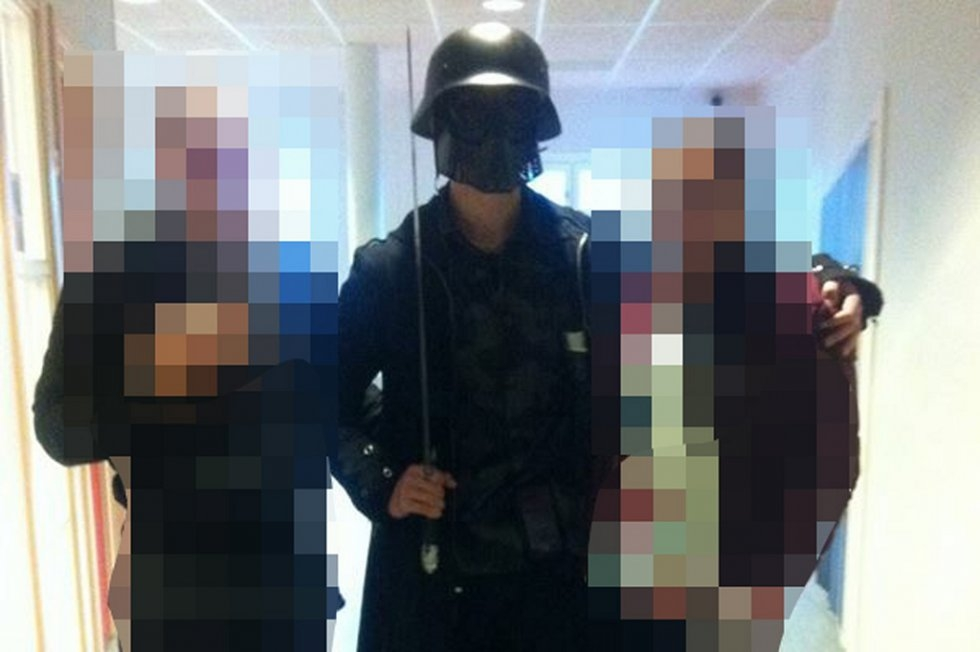 The masked attacker poses for a photo with students. who didn't realize who he was, before launching his assault/ (AFP)
