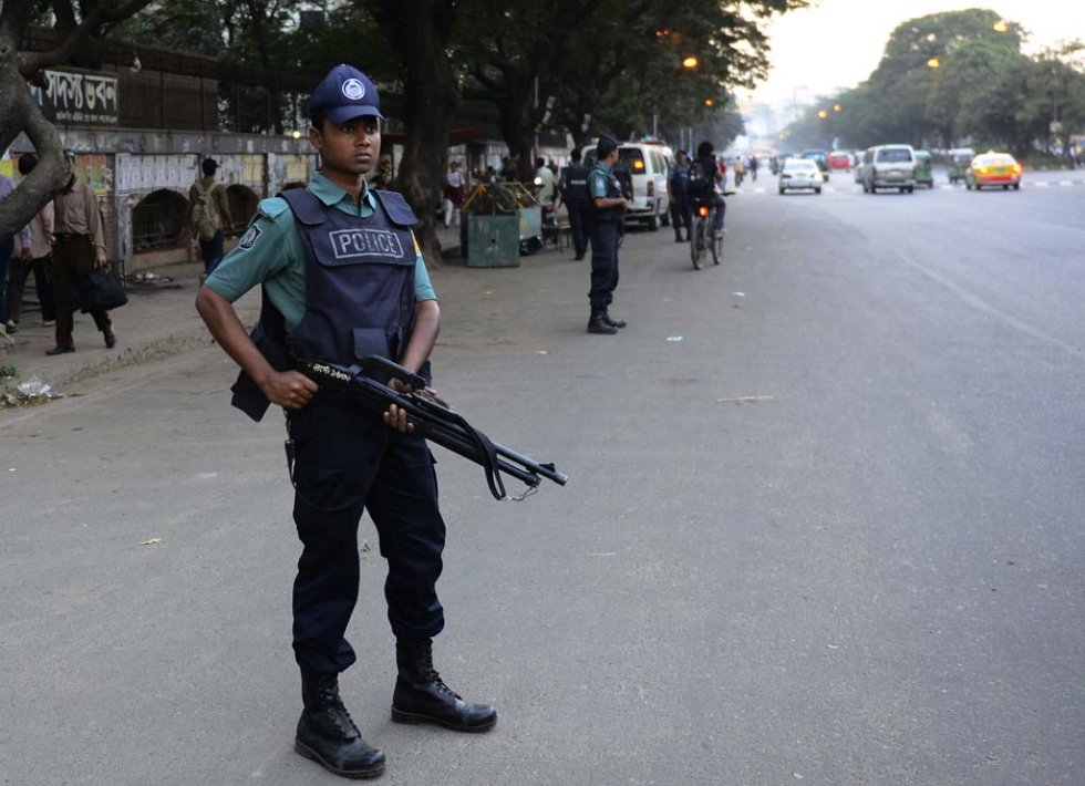 A policeman stands guard in Dhaka after executions of two opposition leaders. November, 2015.