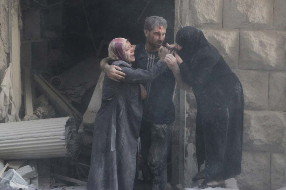 Syrians stand amid debris following an air strike by government forces in the northern city of Aleppo on July 15, 2014