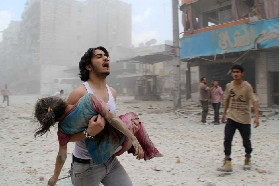 A man carries his sister, who was injured in a barrel-bomb attack by government forces against a rebel-held district of Aleppo on June 3, 2014