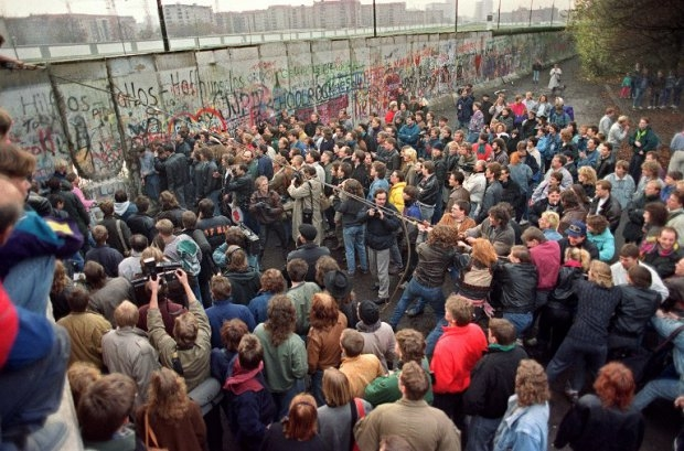 Berliners demolish a section of the wall in order to open a new crossing point between the East and the West early 11 November 1989 (AFP Photo / Gerard Malie)