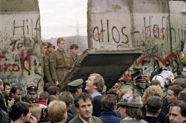 East German border guards demolish a section of the Berlin Wall early November 11, 1989