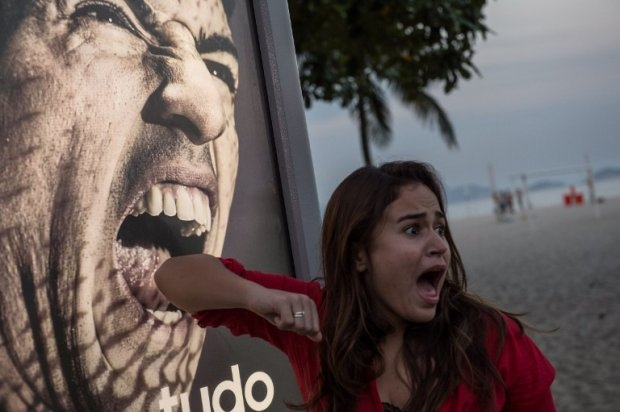 A tourist jokes in front of an advertisement showing Luis Suarez, in Rio de Janeiro, June 26, 2014.