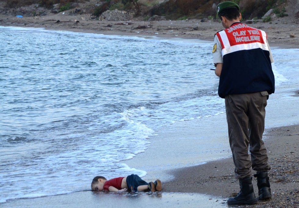 A Turkish police officer stands next to a migrant child who drowned off Bodrum, southern Turkey, on September 2, 2015